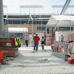 Tent structure being put up at the base of the right-field wall -