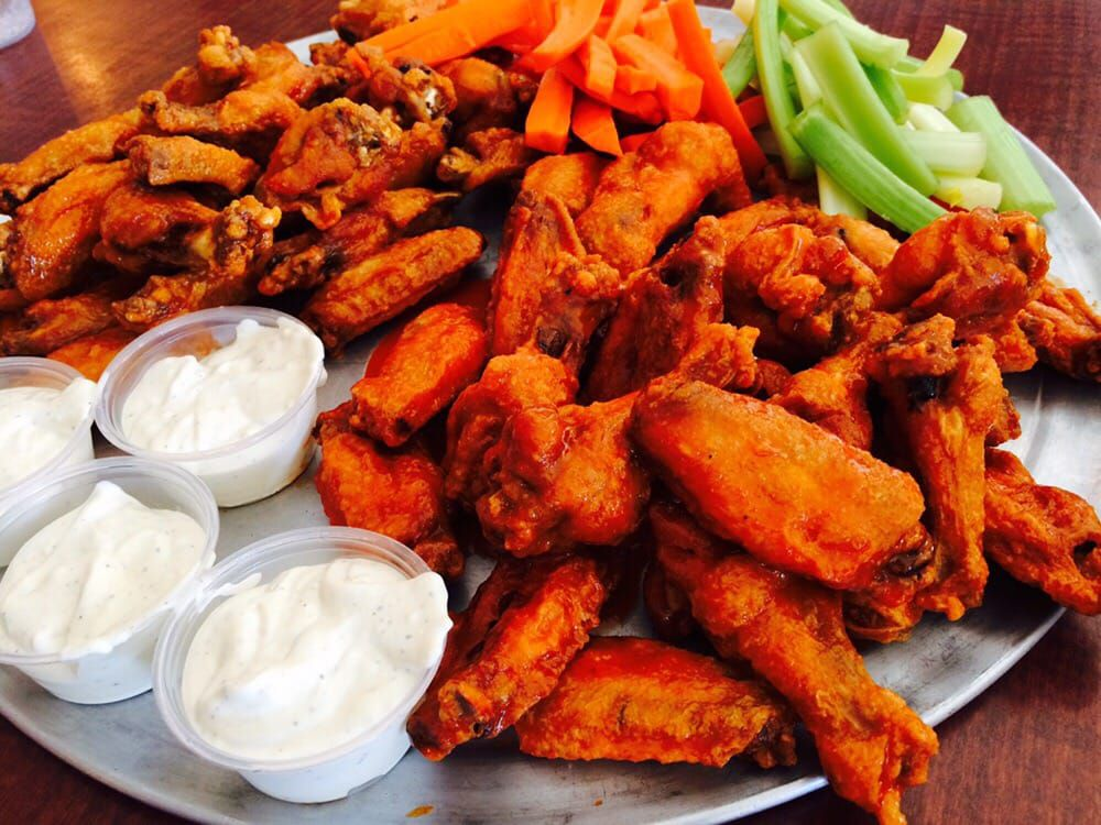 A plate of bright orange hot wings shown from above.