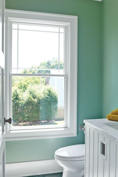 Large rectangle window with white frames in a small bathroom.
