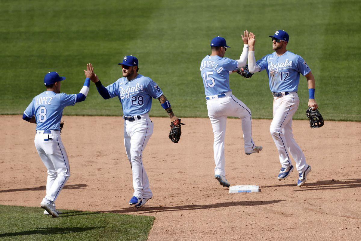 Nicky Lopez #8, Kyle Isbel #28, Whit Merrifield #15 and Hunter Dozier #17 of the Kansas City Royals celebrate after the Royals defeated the Toronto Blue Jays 2-0 to win the game at Kauffman Stadium on April 18, 2021 in Kansas City, Missouri.