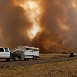 Residents evacuate along Hays Road in Peeples Valley, Ariz. as the Yarnell Hill Fire advances on Sunday, June 30, 2013. The fire started Friday and picked up momentum as the area experienced high temperatures, low humidity and windy conditions. It has forced the evacuation of residents in the Peeples Valley area and in the town of Yarnell. (AP Photo/The Arizona Republic, Tom Story)