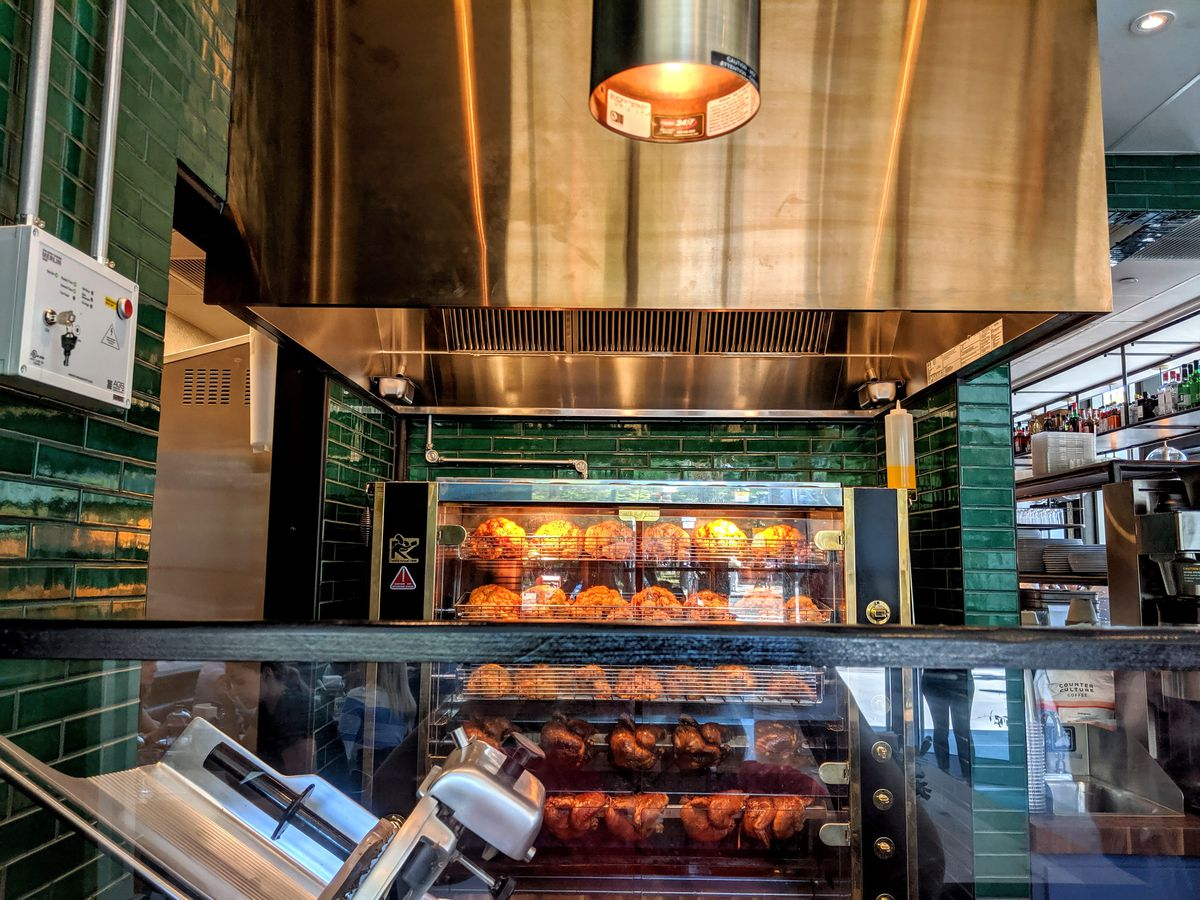 A rotisserie oven is full of rows of cauliflower and chicken