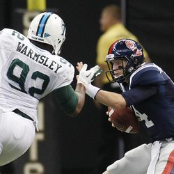 Mississippi quarterback Bo Wallace (14) tries to elude the rush of Tulane defensive tackle Julius Warmsley (92) in the first half of an NCAA college football game in New Orleans,  Saturday, Sept. 22, 2012. Wallace was sacked on the play.