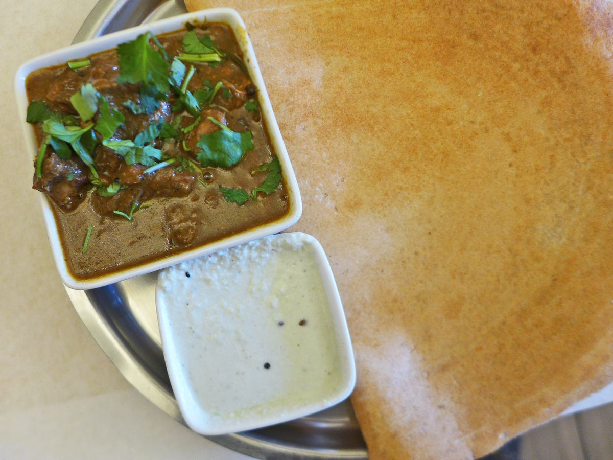 A browned pancake in the background with a square bowl of brown stew and dish of white yogurt.