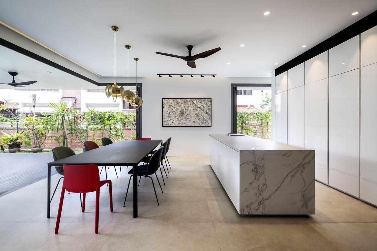 Kitchen opening onto concrete terrace.