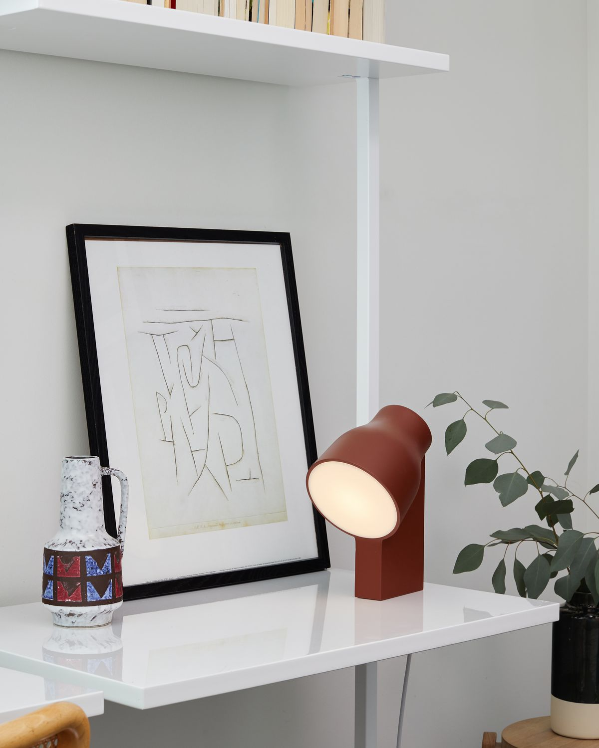 Red table lamp on desk.