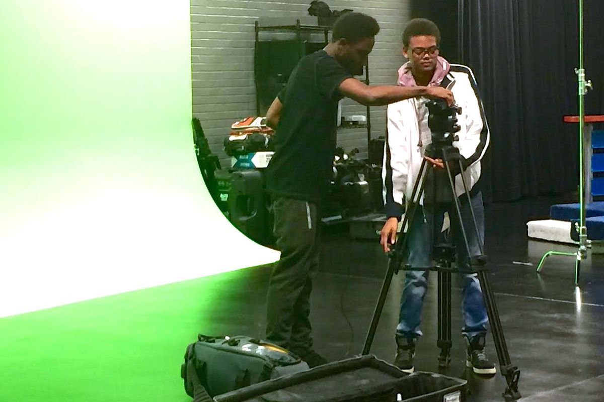 Davoni White (left) and Chris Patterson (right) rush to set up a camera in one minute during an advanced studio production class at Warren Central High School. The FrontRunner studio (pictured here) was funded by the Race to the Top grant.
