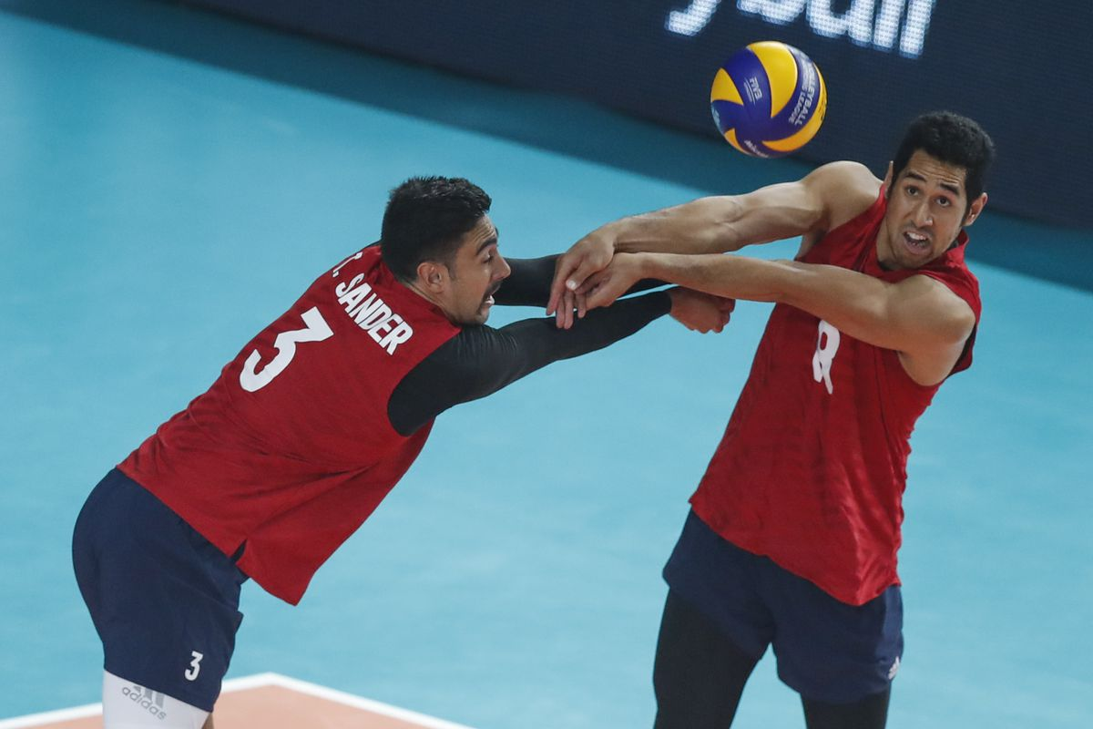 USA's Taylor Sander and USA's Garrett Muagututia receive the ball against Russia during the FIVB Volleyball Nations League first place game in Chicago, Illinois, July 14, 2019.