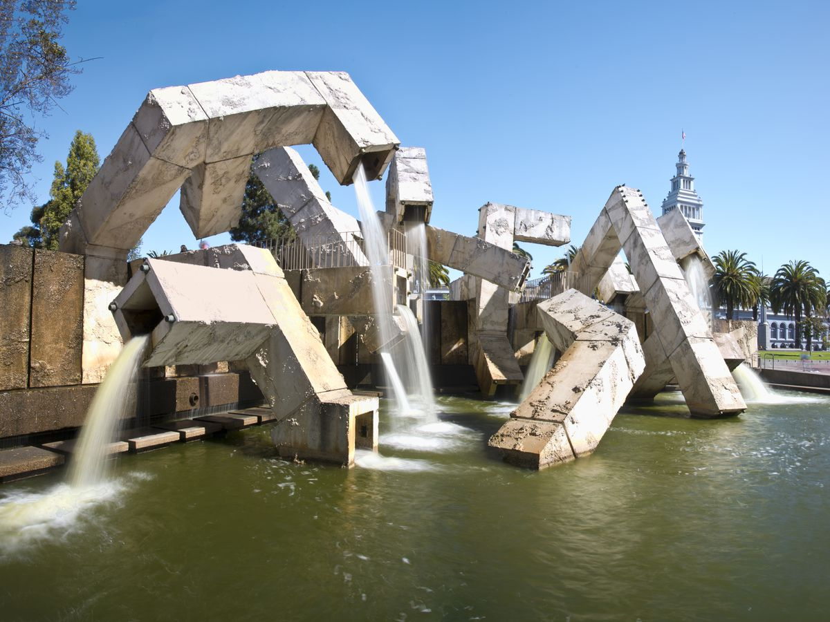 A snaking and cube-like fountain made up of concrete. It looks rough and undone, and gushes water into a pool.