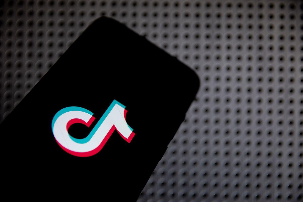 An image of the TikTok logo on a black phone screen.