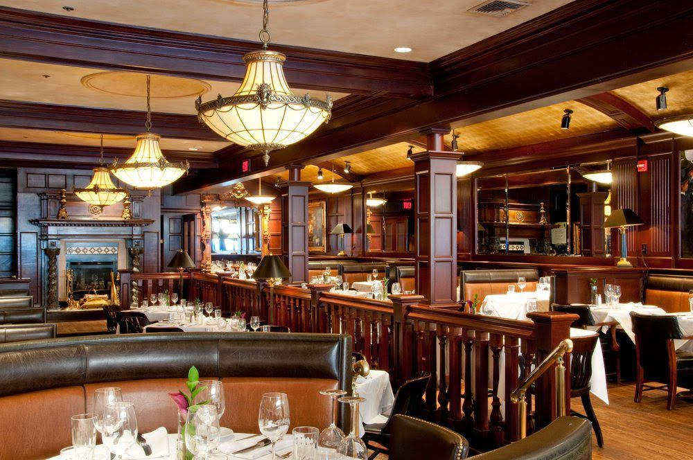 A restaurant with wooden beams on the ceiling, brown banquette seating, and white tablecloths