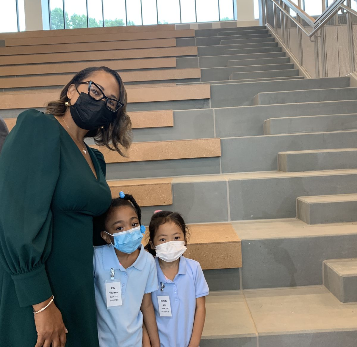 A woman wearing a green dress, black mask and glasses poses for a picture with two young girls, both wearing blue shirts and protective masks.