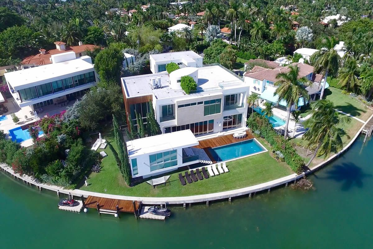 Aerial of a modern two-story waterfront home in Miami Beach with a pool and gazebo out back along with a rooftop terrace.