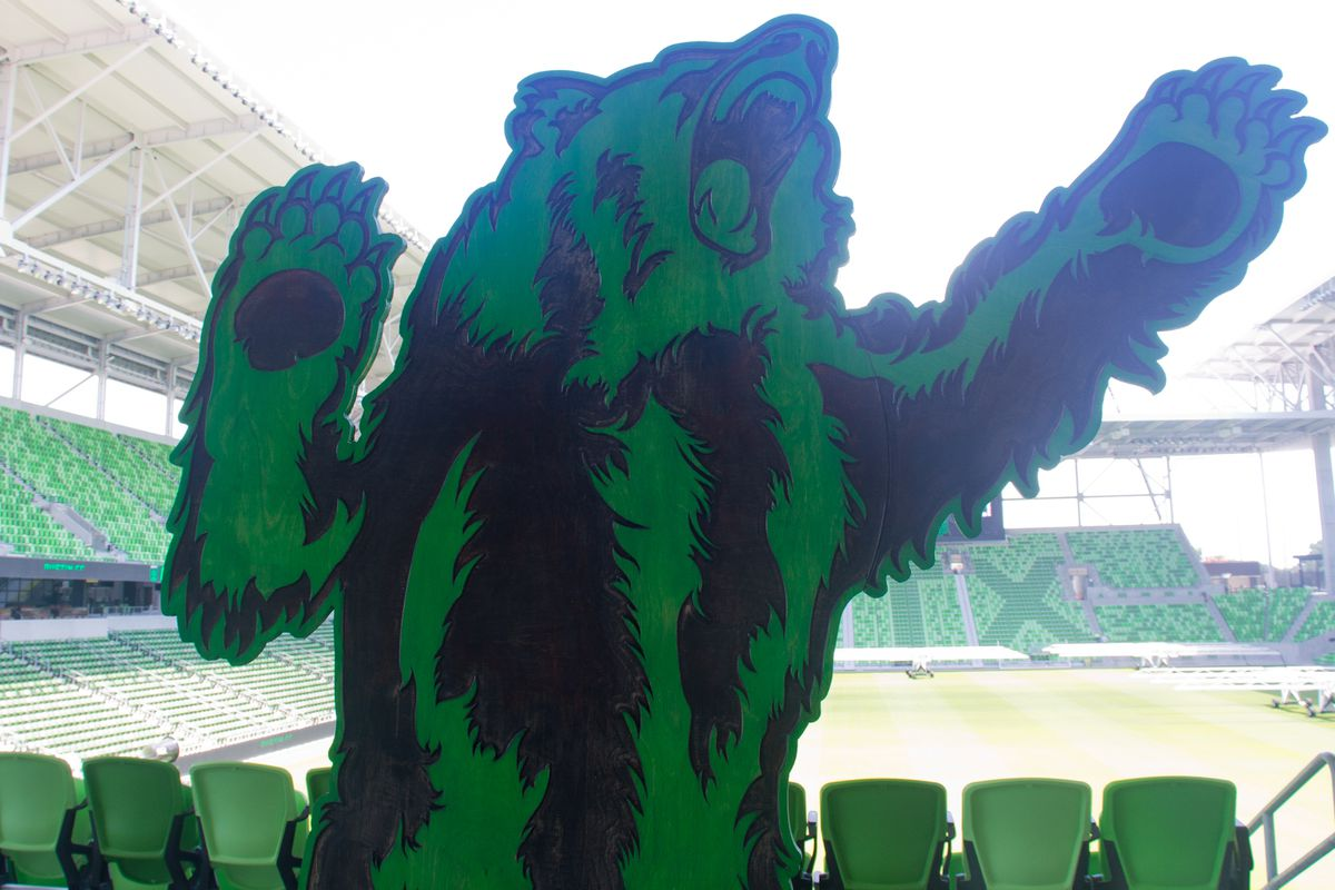 A black-and-green bear cutout figure in front of a soccer field