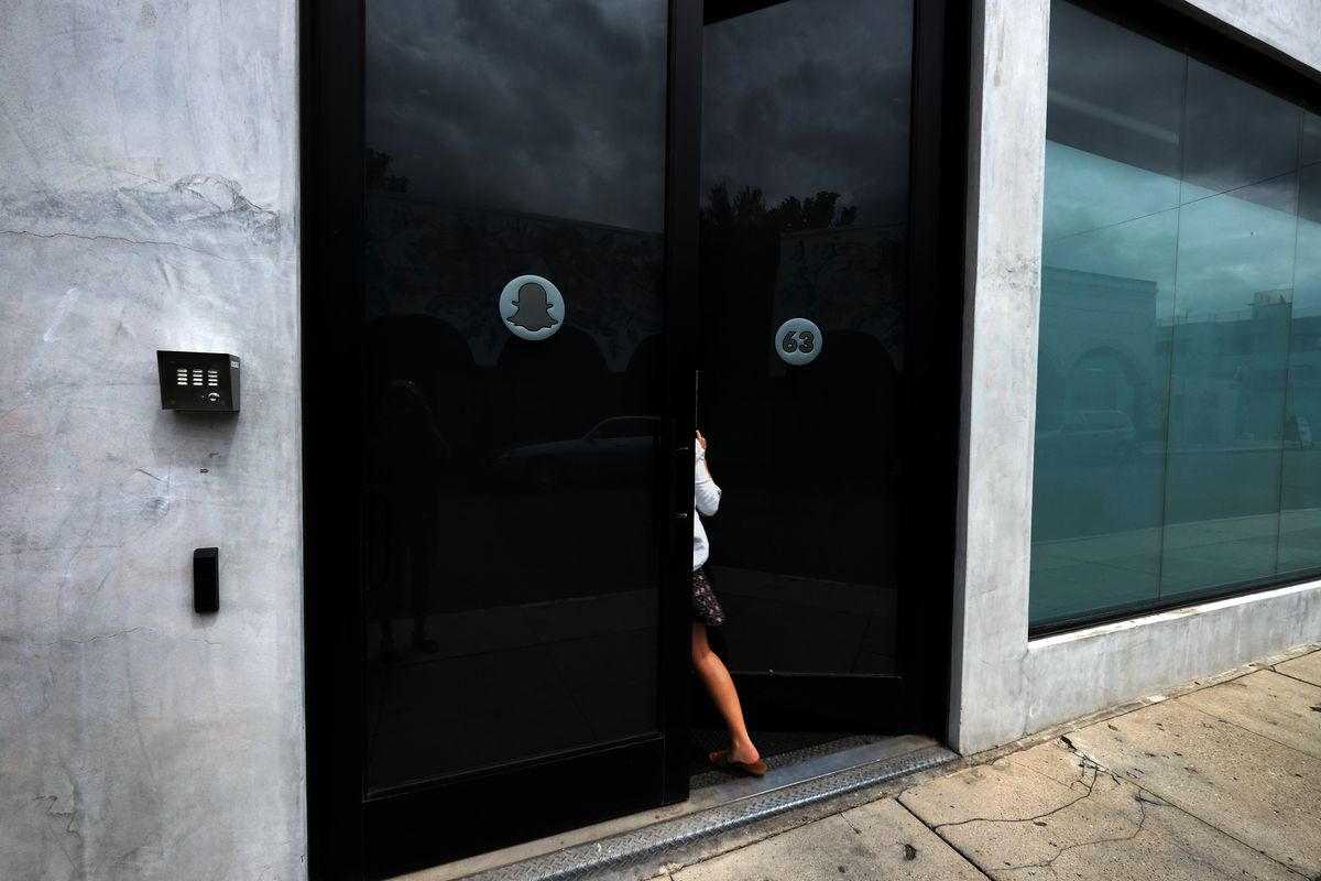A person disappearing behind a Snapchat office door.