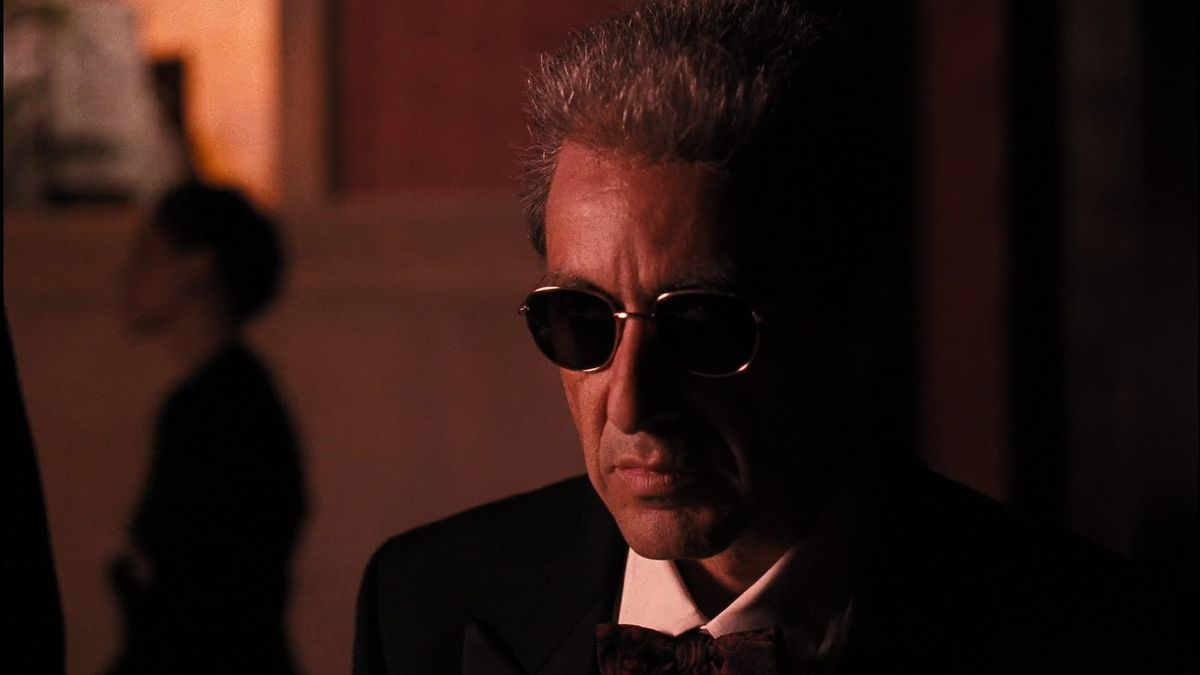 michael corleone wears round sunglasses and stares into the bright sun in The Godfather Part III