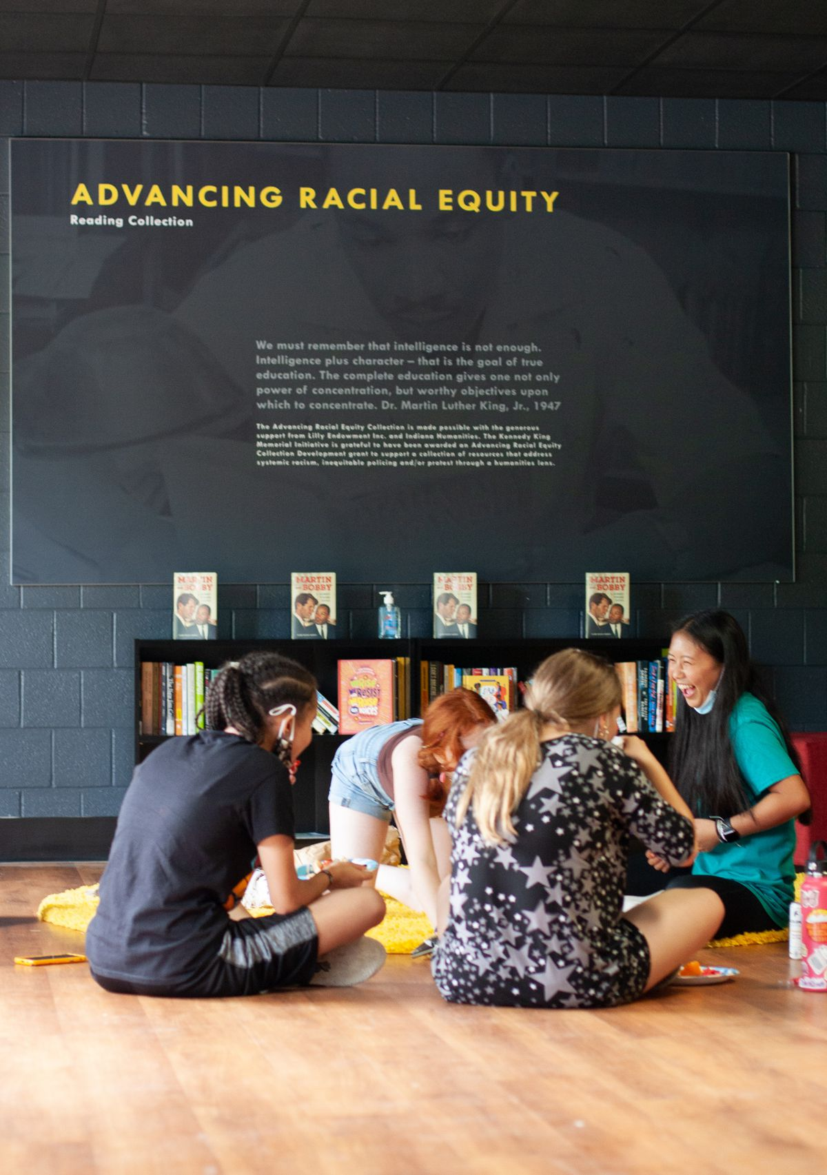 """Four teens sit on a hardwood floor in front of a bookshelf eating lunch. A girl in a blue shirt laughs on the far right while the three others look at her. The teens are sitting in front of a sign on the wall that reads """"advancing racial equity"""""""