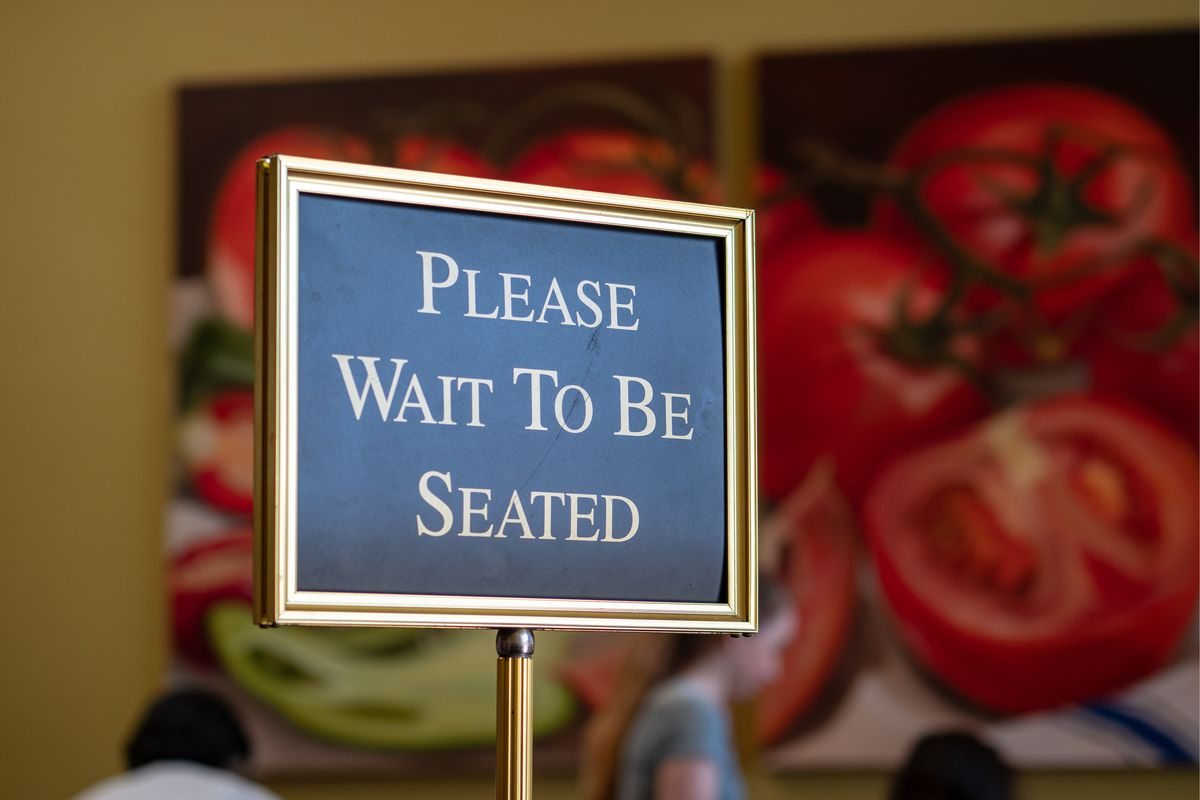 """A sign at a restaurant that says, """"Please Wait to Be Seated"""""""