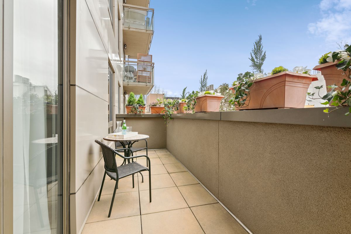 A balcony with several planters and a small table with two chairs.