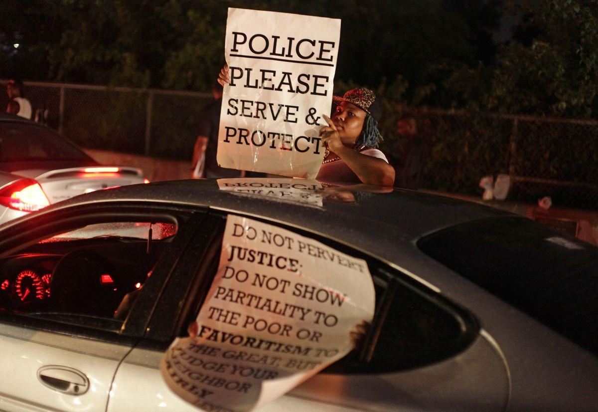 Ferguson police serve protect sign
