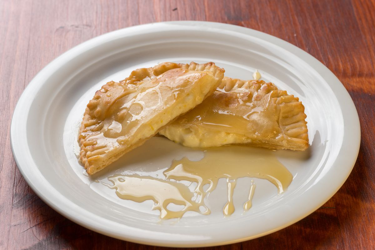 A cheese-filled seadas is cut in half on a plate with honey