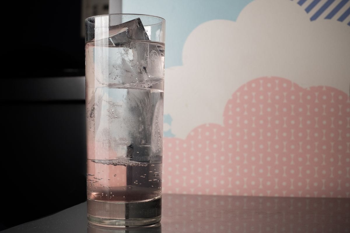 A collins glass filled with clear ice, a slightly pink base, but clear drink, on a table in front of pastel-colored wallpaper that looks like clouds.