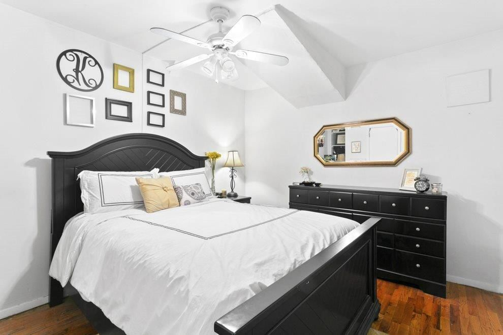 A bedroom with a large bed, white walls, a ceiling fan, and hardwood floors.