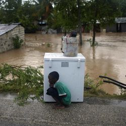 A boy tries to take cover from the cold behind an appliance sitting higher than the floodwaters triggered by Tropical Storm Isaac in Port-au-Prince, Haiti, Saturday Aug. 25, 2012. Tropical Storm Isaac swept across Haiti's southern peninsula early Saturday, dousing a capital city prone to flooding and adding to the misery of a poor nation still trying to recover from the 2010 earthquake.