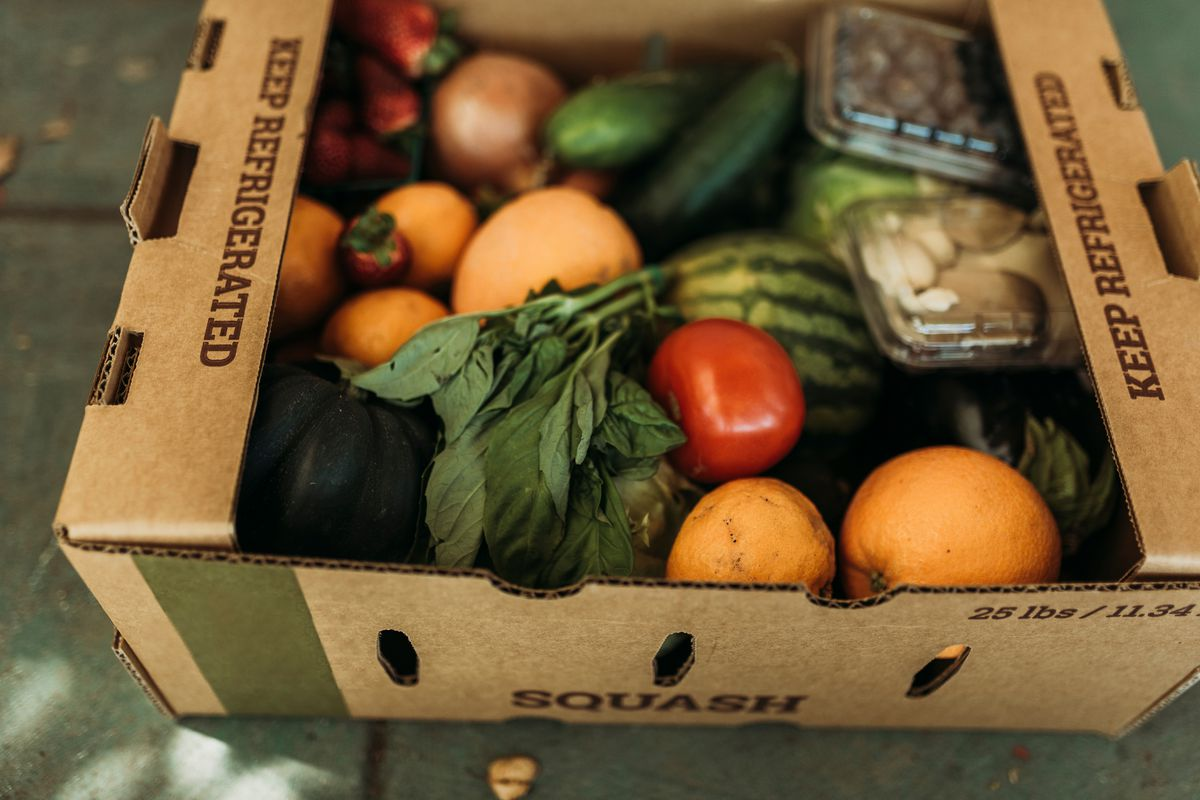 A cardboard box filled with various produce.