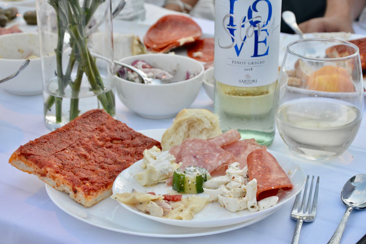 table setting with wine, antipasto, and a slice of tomato pie