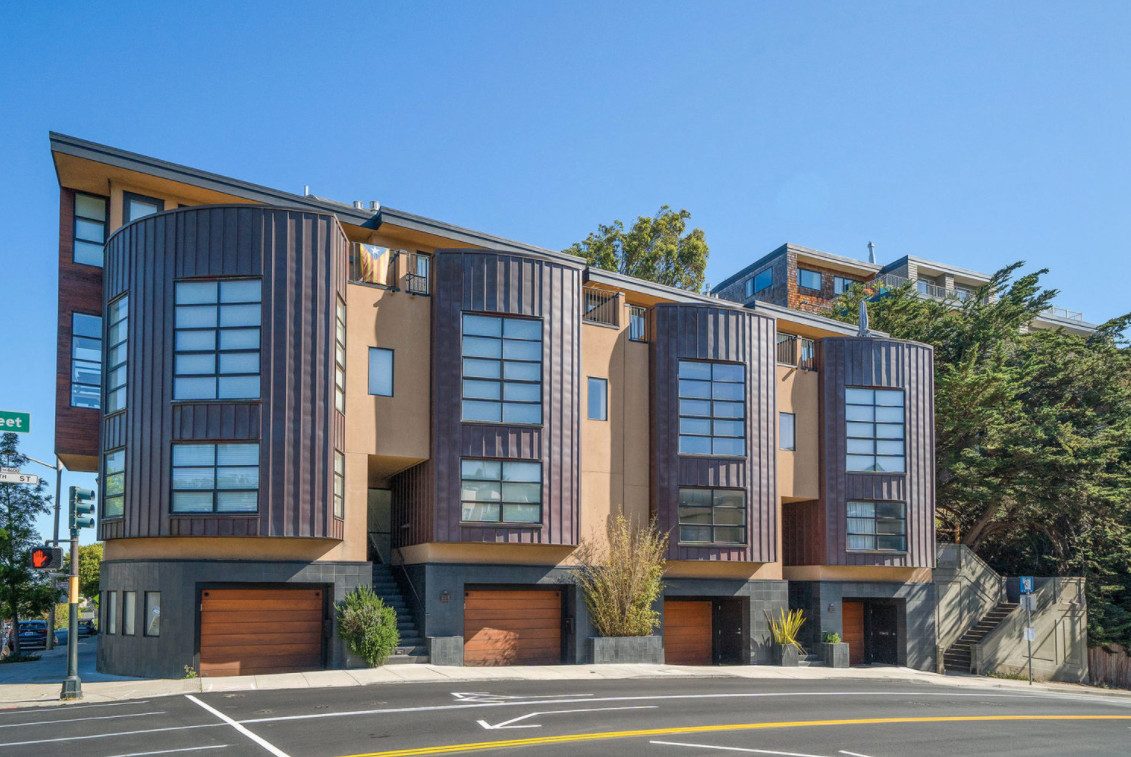 A series of contemporary townhouses in a row with a peaked, angled roof. The facade is painted in shades of orange and brown.