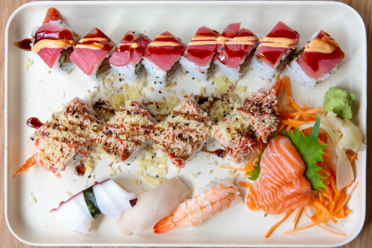 A white tray of sushi and sushi rolls, sashimi, rice
