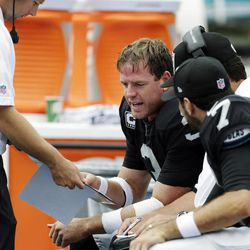 Oakland Raiders quarterback Carson Palmer (3) reviews plays on the sidelines with quarterback Matt Leinart (7) during the second half of an NFL football game against the Miami Dolphins, Sunday, Sept. 16, 2012, in Miami.
