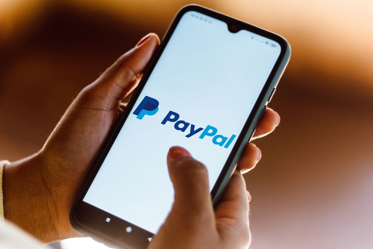 A person opening the PayPal app on their phone