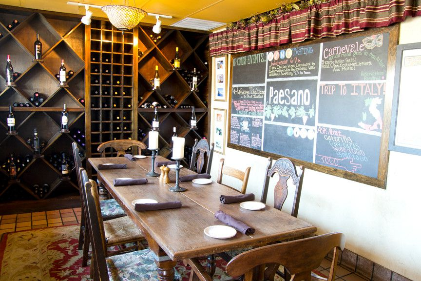 A dark wood, diamond-shaped wine display takes up the whole wall behind a long wood table and a wall with a chalkboard.