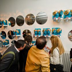 Winners and nominees gather round the wall of prizes.