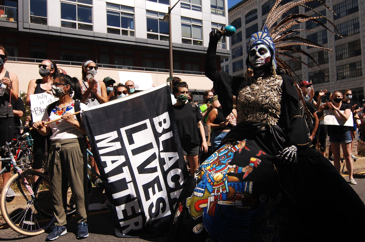A woman holds a Black Lives Matter flag; behind her is a dense crowd of people. In front of her, a woman in a black dress, her face painted like a skull. She raises a jade shaker, and has on a blue headpiece.
