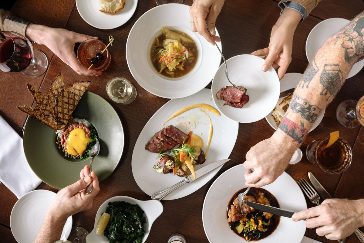 An overhead shot of tartare, duck, greens, escargot bordelaise, and cocktails at Paley's Place