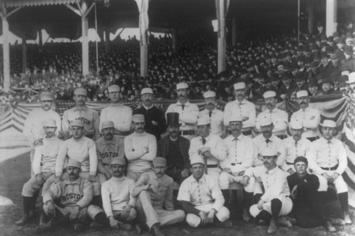 Note the raised middle finger of the hand resting on the shoulder of the player in front of him