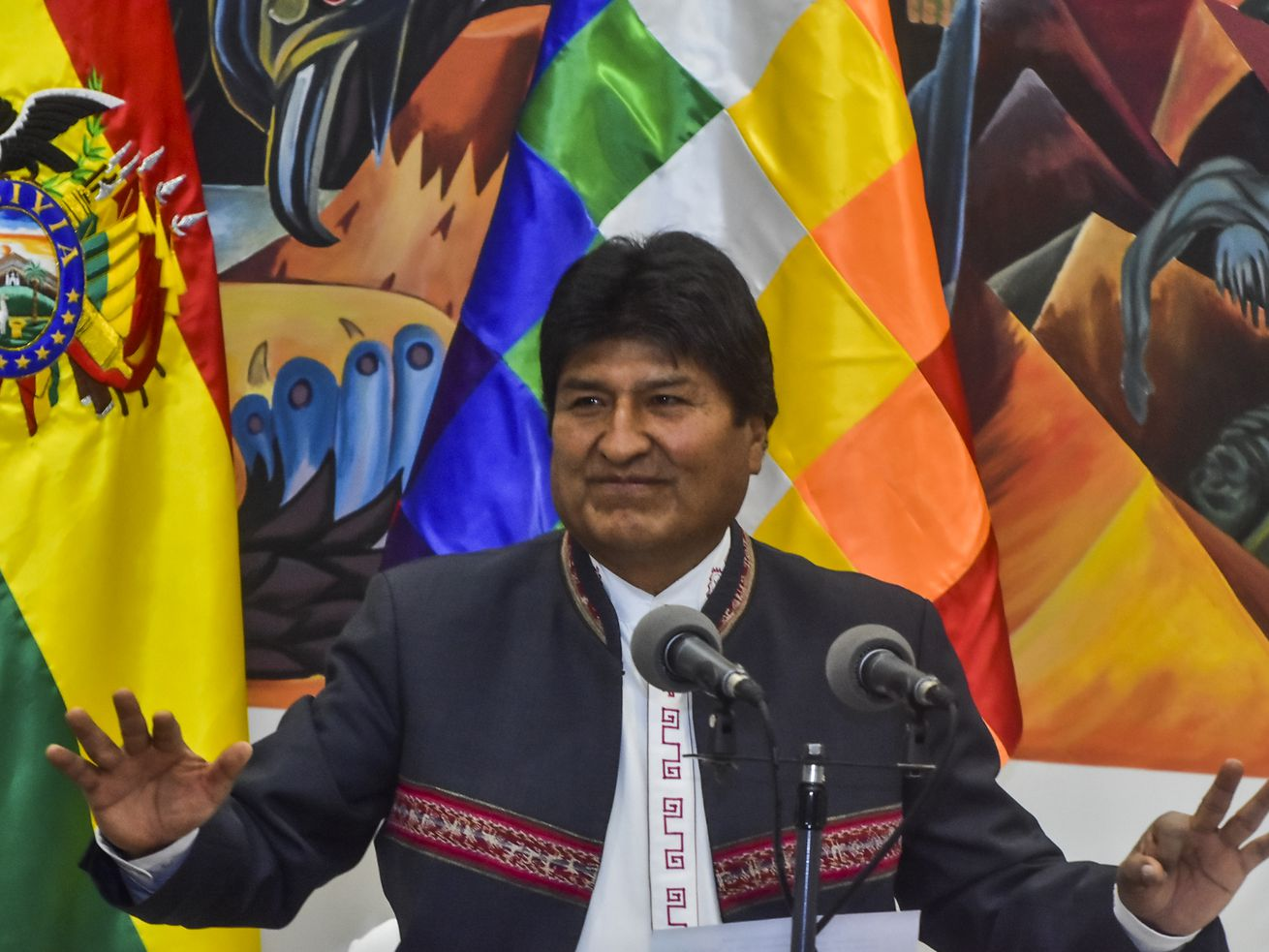 President Evo Morales speaks at a press conference, his arms outstretched. The photo takes place days after his re-election as president, which has been contested as fraudulent.