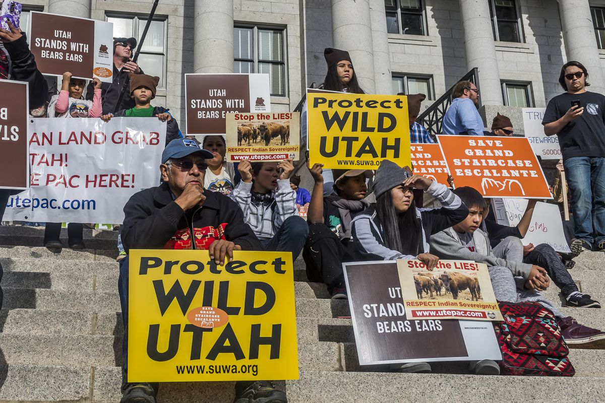 """People sit on the capital building's stone steps holding signs saying """"Protect Wild Utah"""" and """"Utah Stands With Bears Ears."""""""