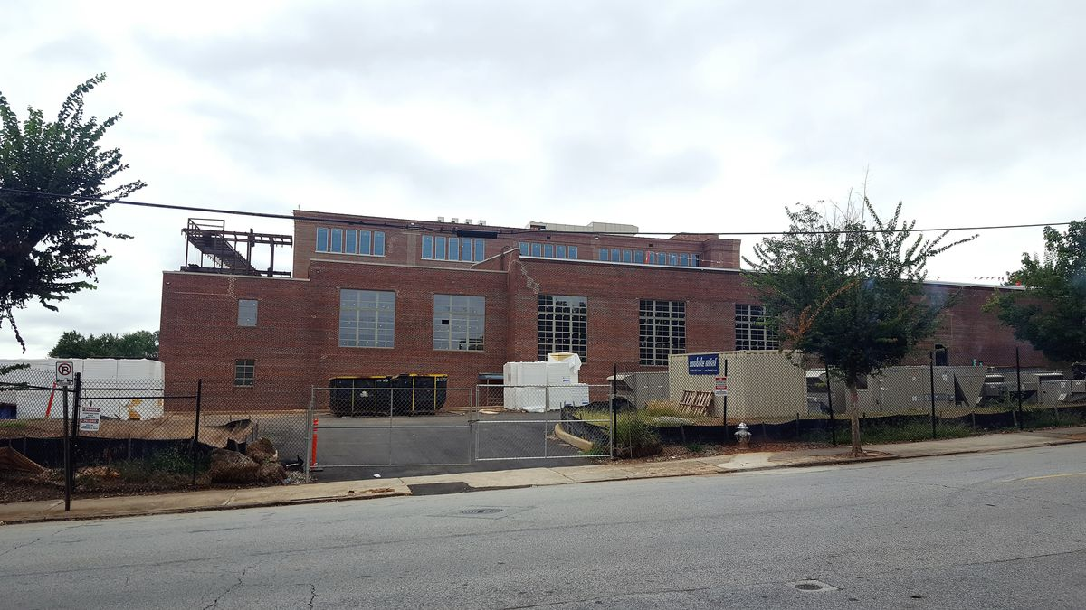 Another view of the old brick building, surrounded by construction fencing and equipment.