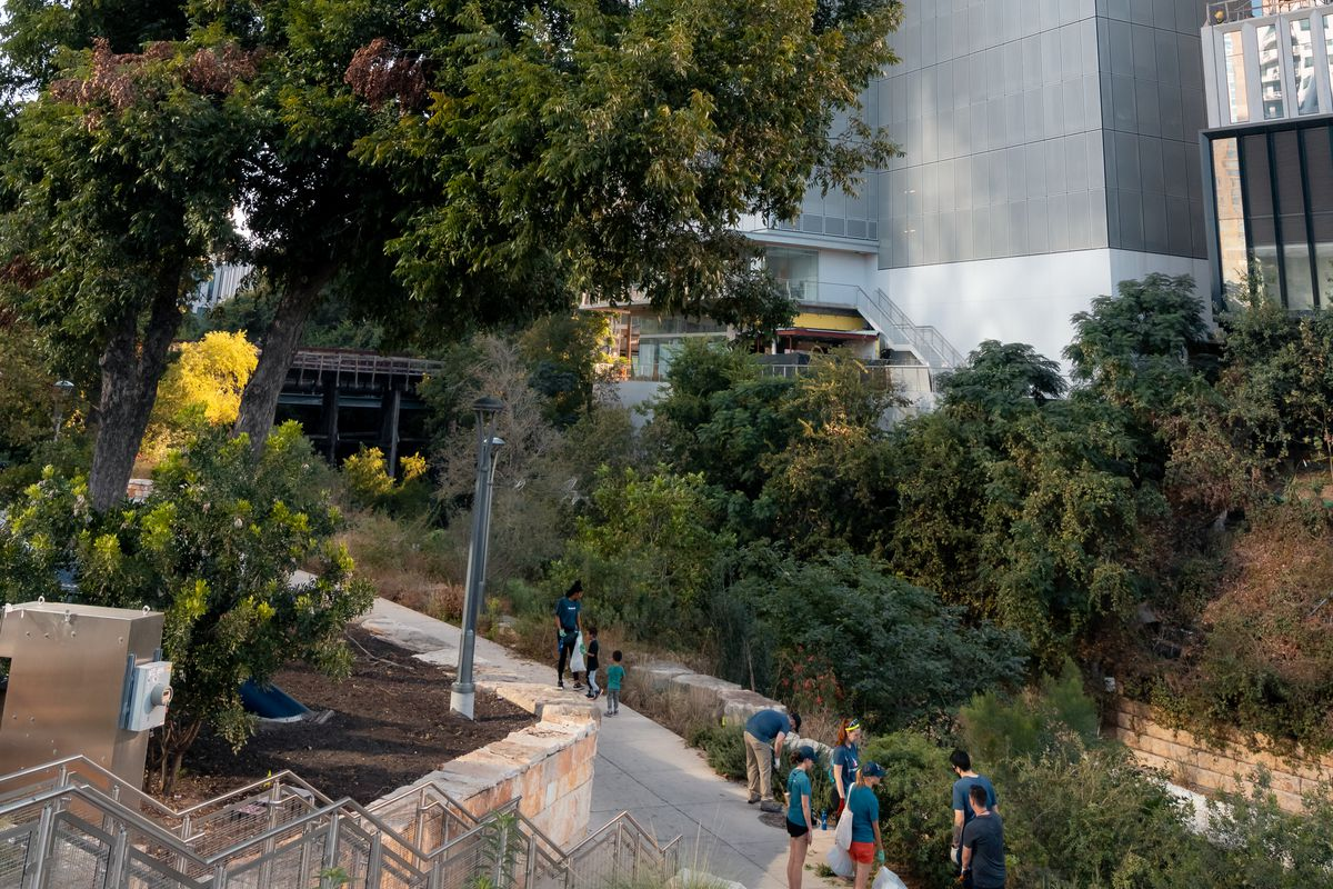 The bottom of a tall building with a mass of trees and a trail in front. There are people in bright safety vests working on the trail.