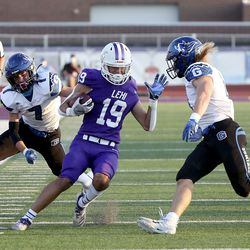 Lehi's Isaiah Tauai (19) runs with the ball between Pleasant Grove's Kolton Bayles (7) and Rex Connors (4) during a football game at Lehi High School in Lehi on Friday, Sept. 11, 2020.