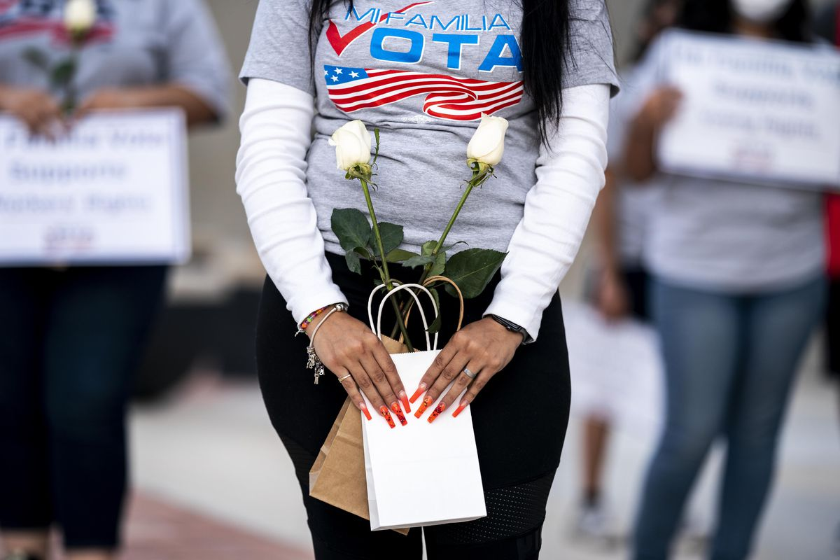 """A Latina woman wearing a shirt that reads """"Mi Familia Vota"""" and carrying two small bags with a white long-stem rose in each."""