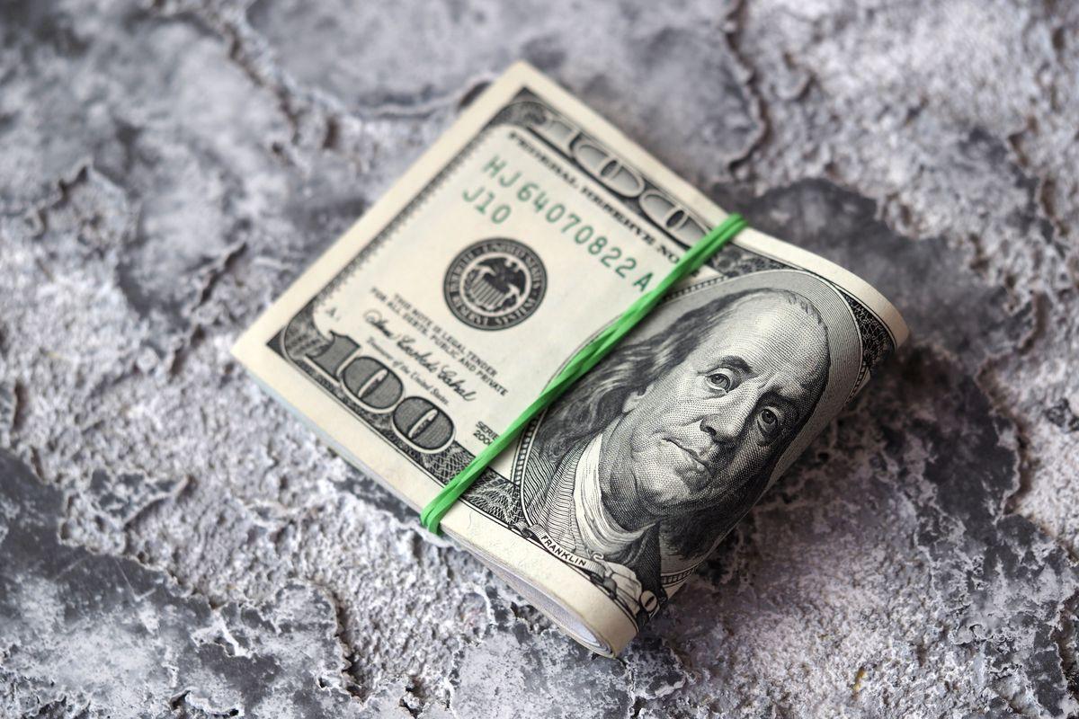 In this photo illustration US dollar bills are seen...