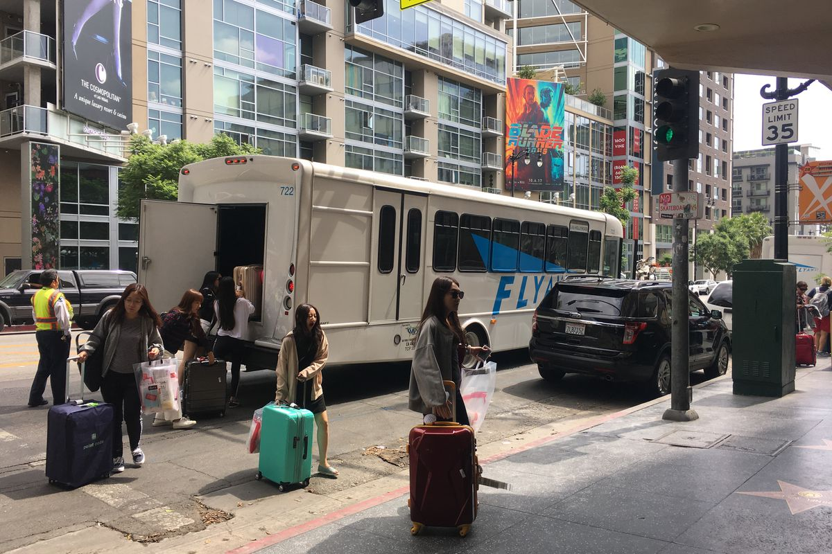 People stand next to a parked bus. Several people have luggage.