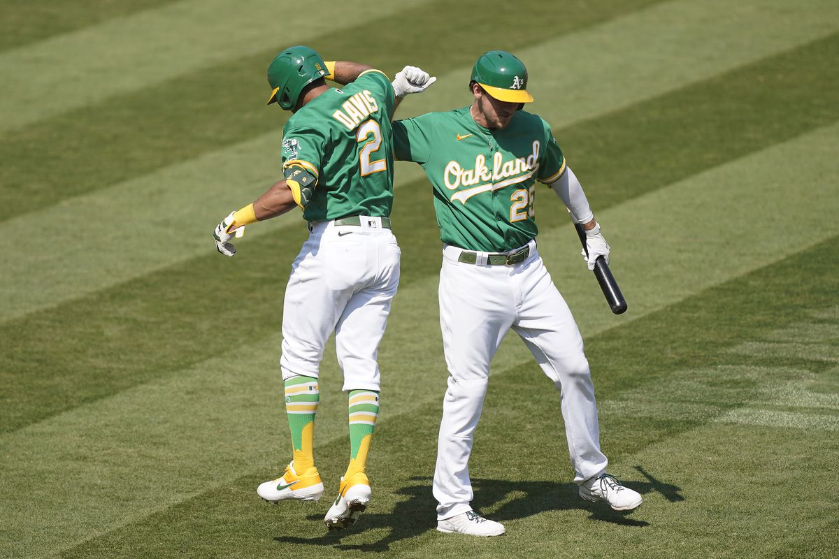 Khris Davis #2 of the Oakland Athletics is congratulated by Stephen Piscotty #25 after Davis hit a solo home against the Chicago White Sox during the fourth inning of Game Two of the American League Wild Card Round at RingCentral Coliseum on September 30, 2020 in Oakland, California.