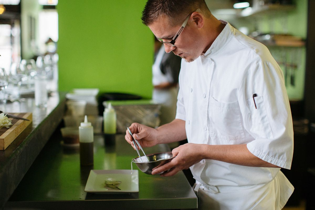 A man wearing glasses and a white chef's coat uses tweezers to lift pickled onions onto a plate from a small metal bowl inside Chartreuse's bright green restaurant space.