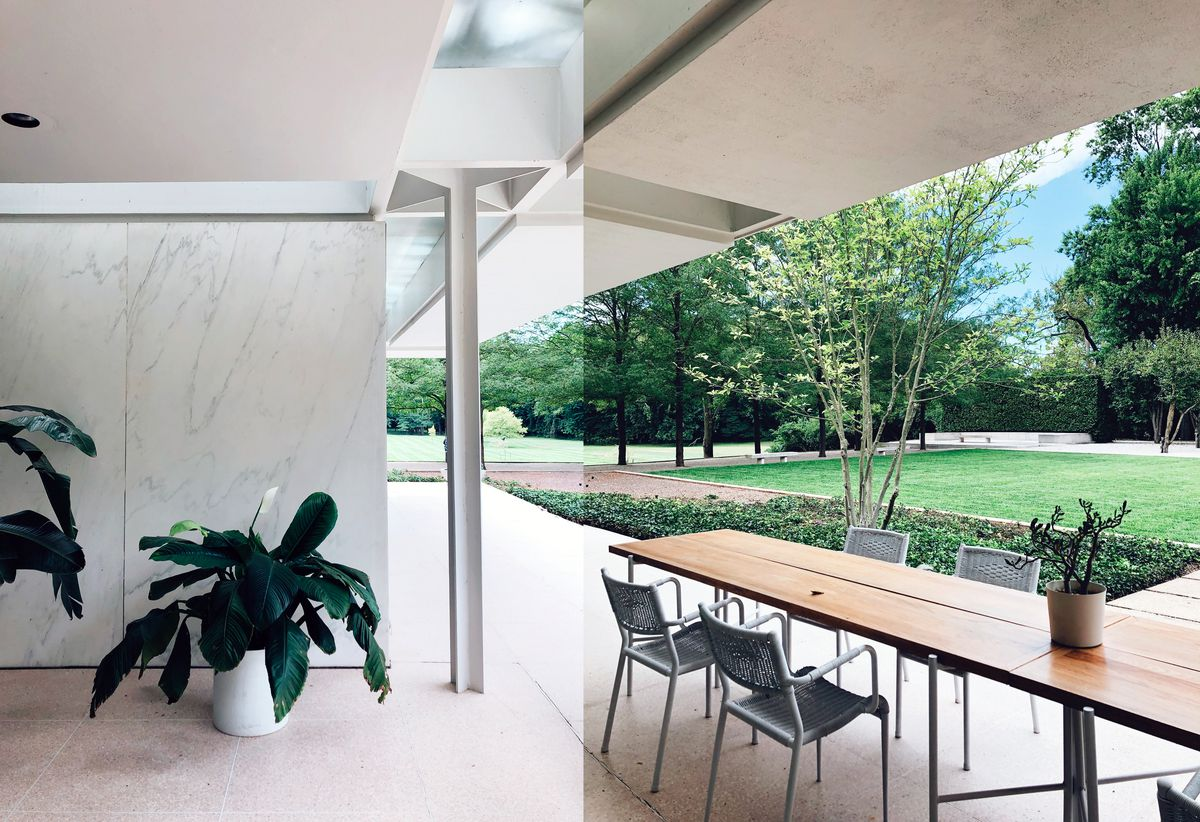 Two images stitched together showing a white marble exterior wall supported by steel columns painted white, with skylights running above a covered patio featuring a long wooden table and white chairs. There's a grassy lawn in the background.